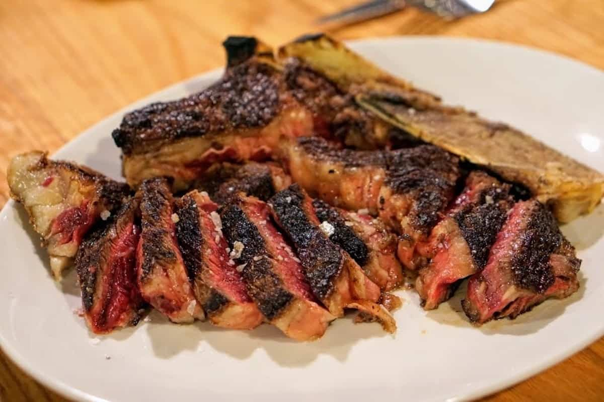 Medium rare steak sliced on a plate and sprinkled with sea salt.