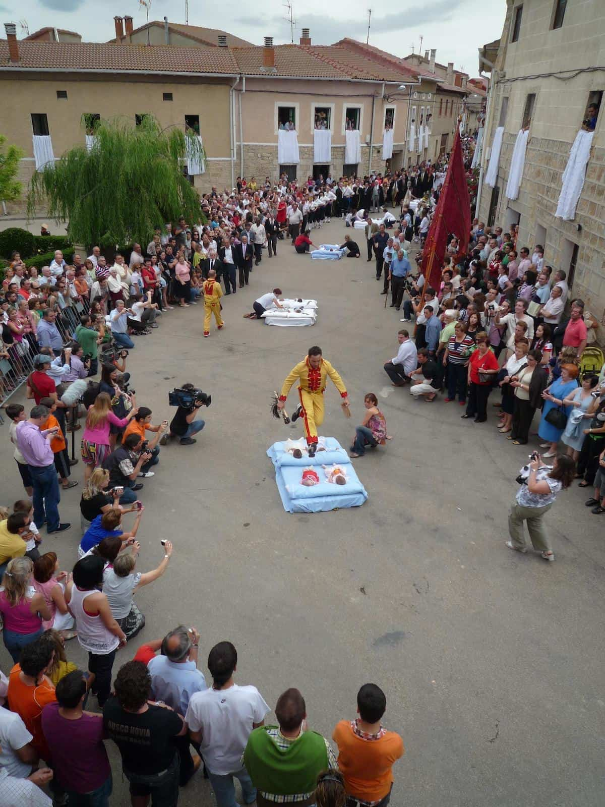 Costumed men jumping over babies laid on mattresses in a village street in Spain