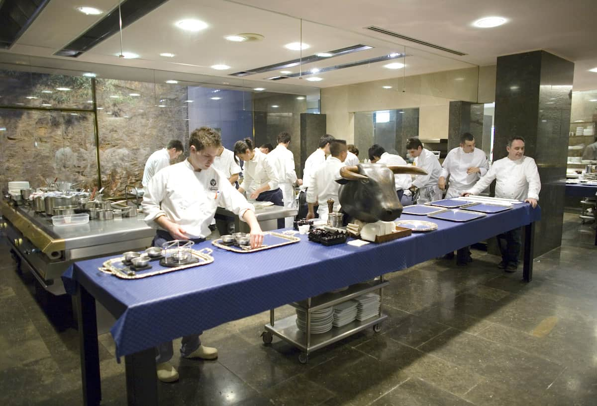 Interior shot of a busy kitchen with people in white cook's jackets cooking.