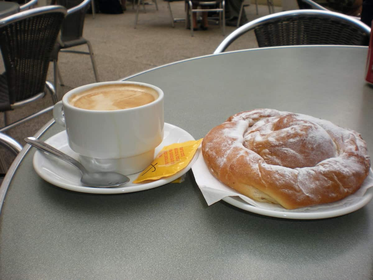 Cup of coffee with milk next to a spiral-shaped pastry dusted with sugar on an outdoor cafe table.