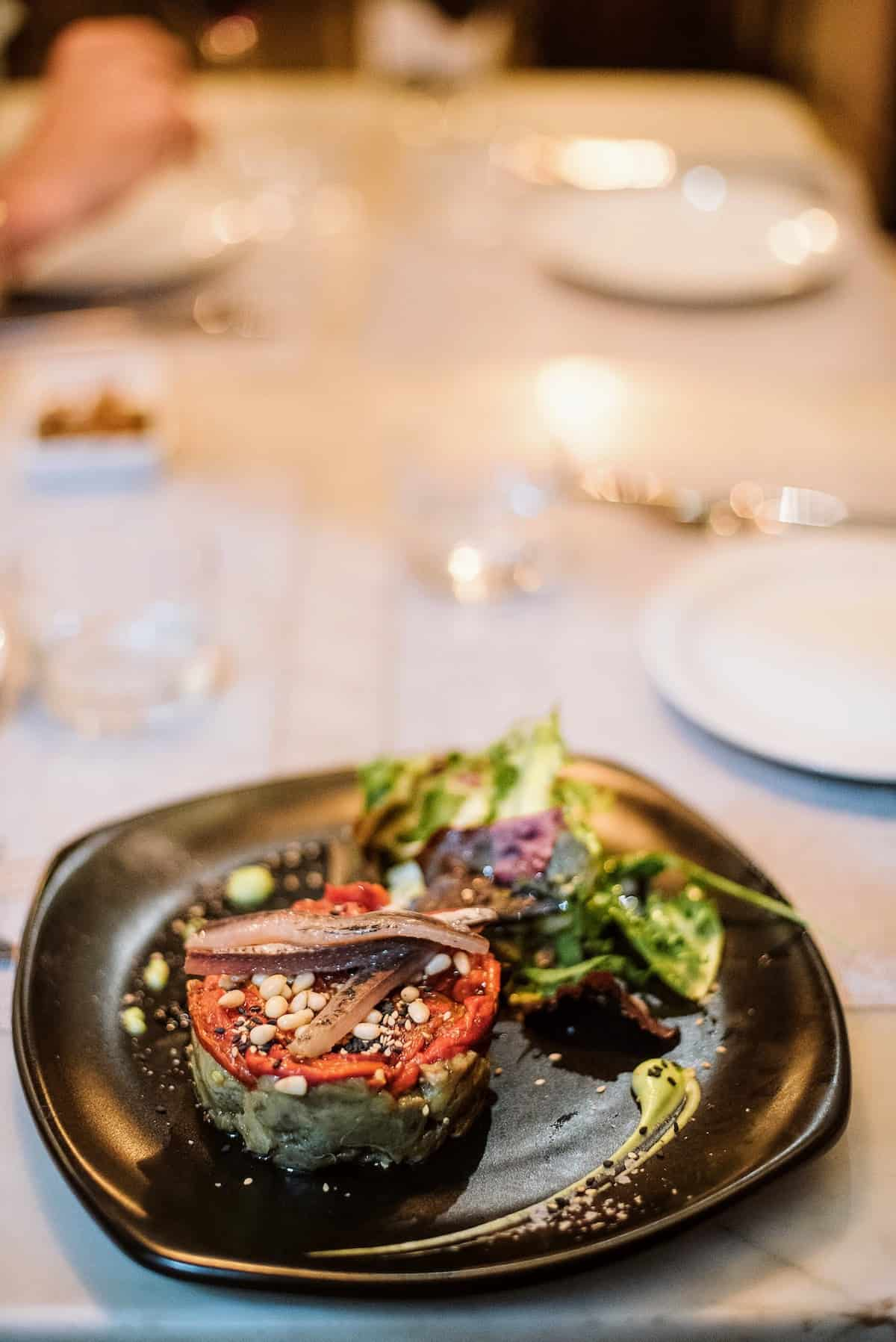 Modern presentation of grilled vegetables and anchovies on a black plate.