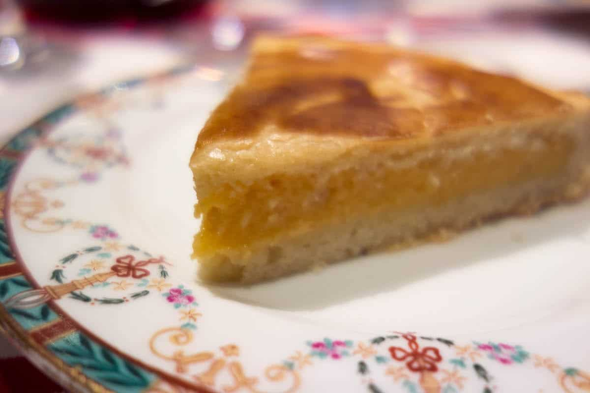Slice of Basque cake filled with pastry cream on a cake.