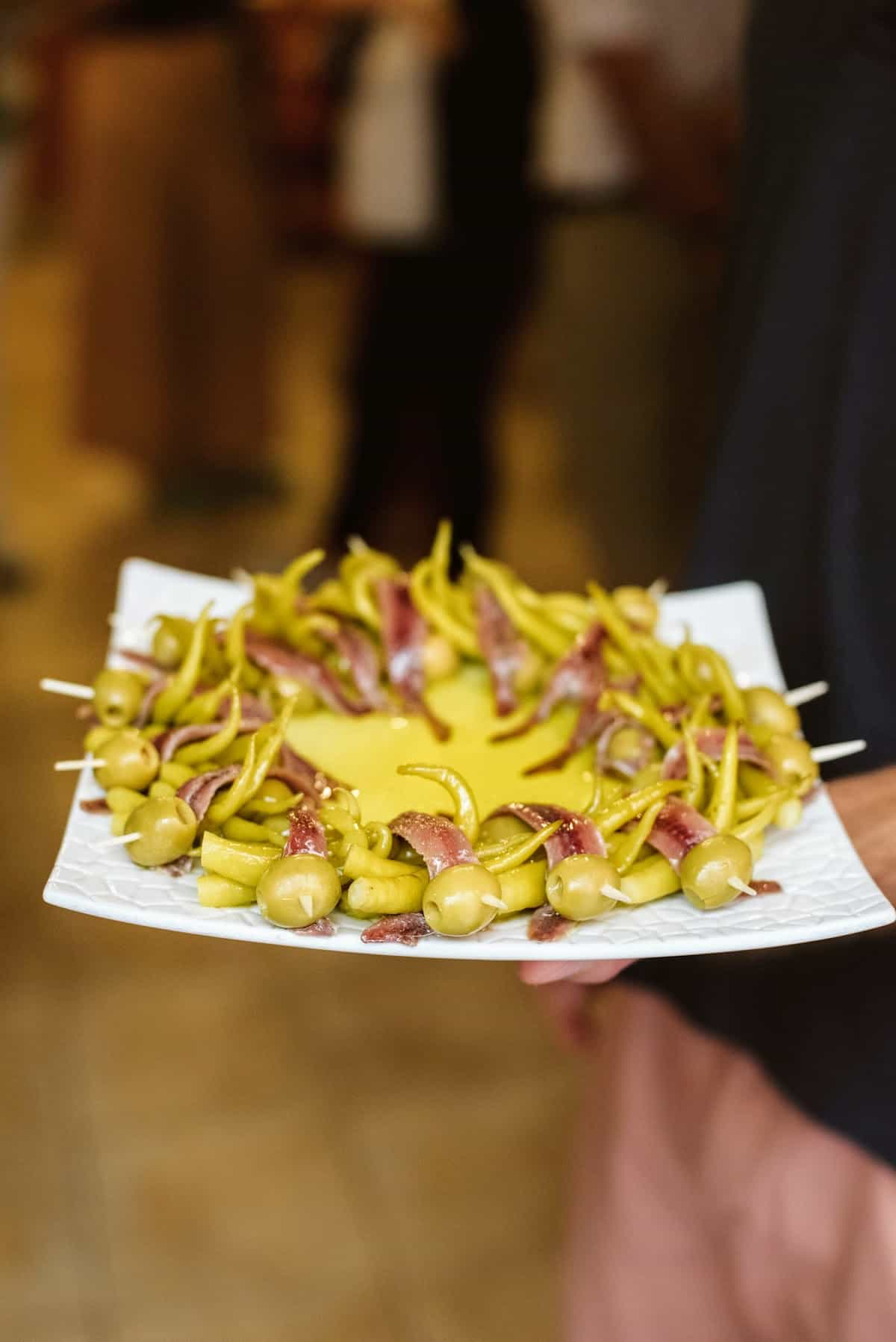 Skewers, or pintxos, of anchovies, peppers, and olives arranged on a plate.