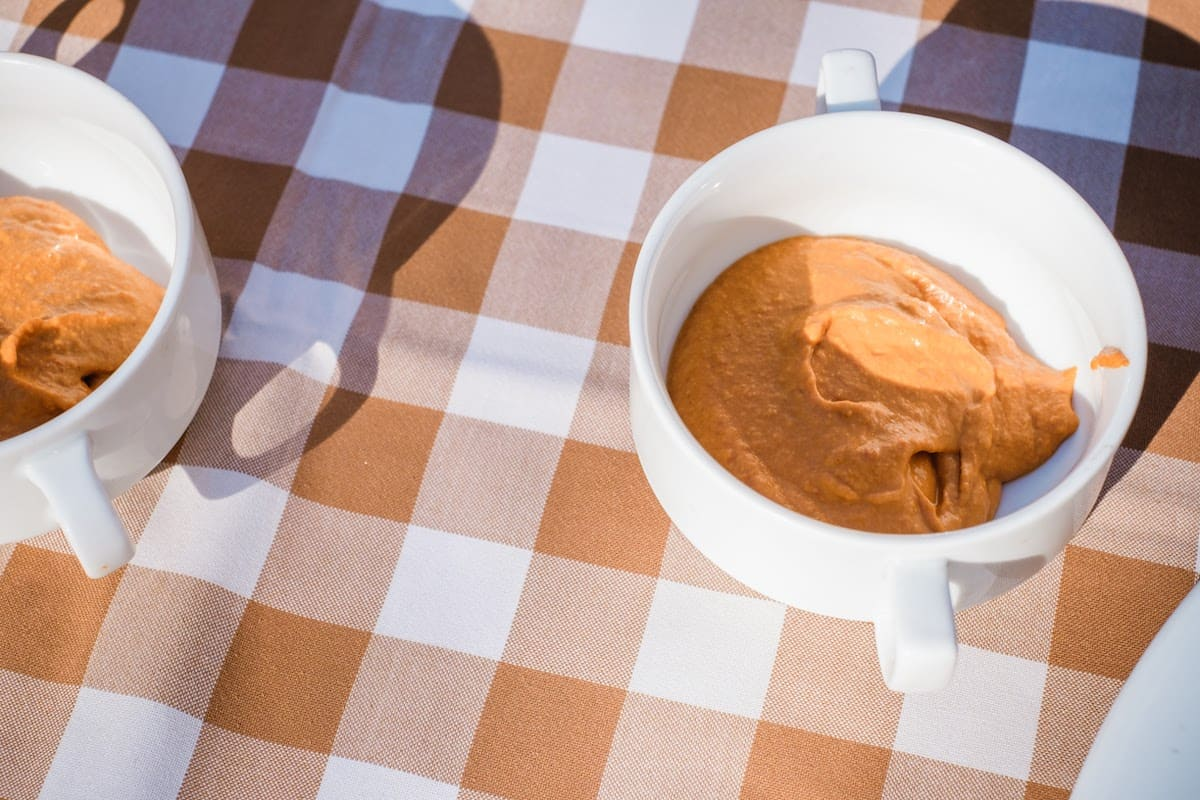 Two white cups of orange-colored romesco sauce on a checkered tablecloth.