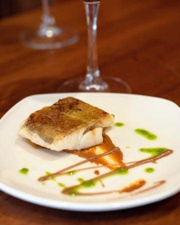 Modern presentation of a cod fillet on a bed of dark orange romesco sauce.