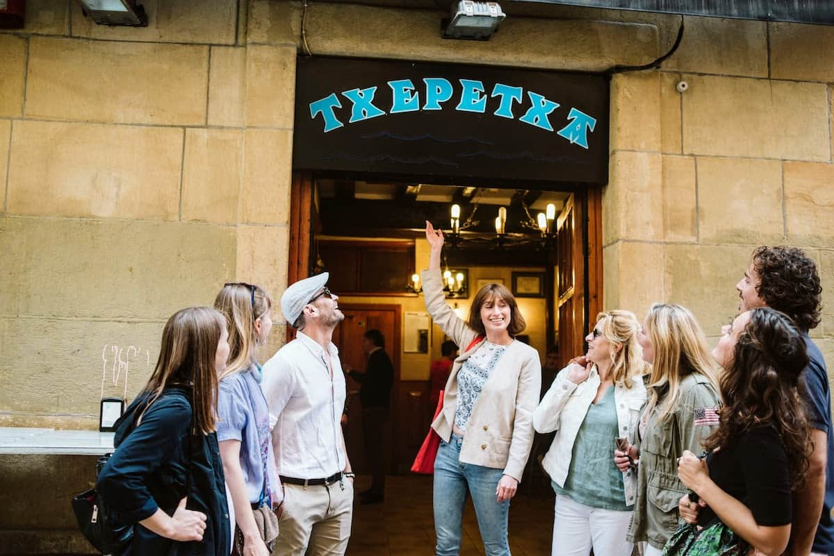 Group of people standing outside a bar named Txepetxa, written in blue lettering on a black background.