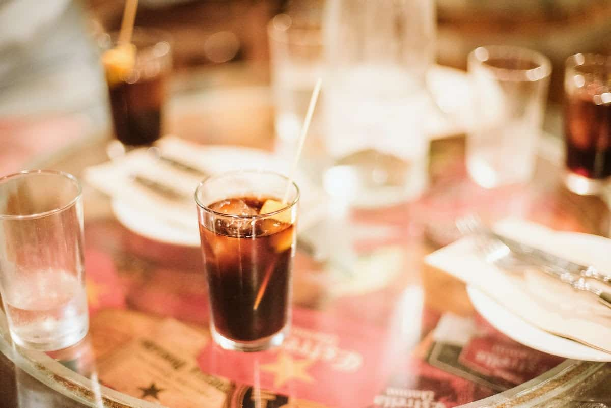Small glass of vermouth on a tabletop.