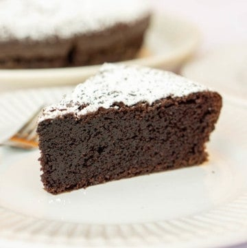 Close up of a slice of chocolate olive oil cake on a white plate.