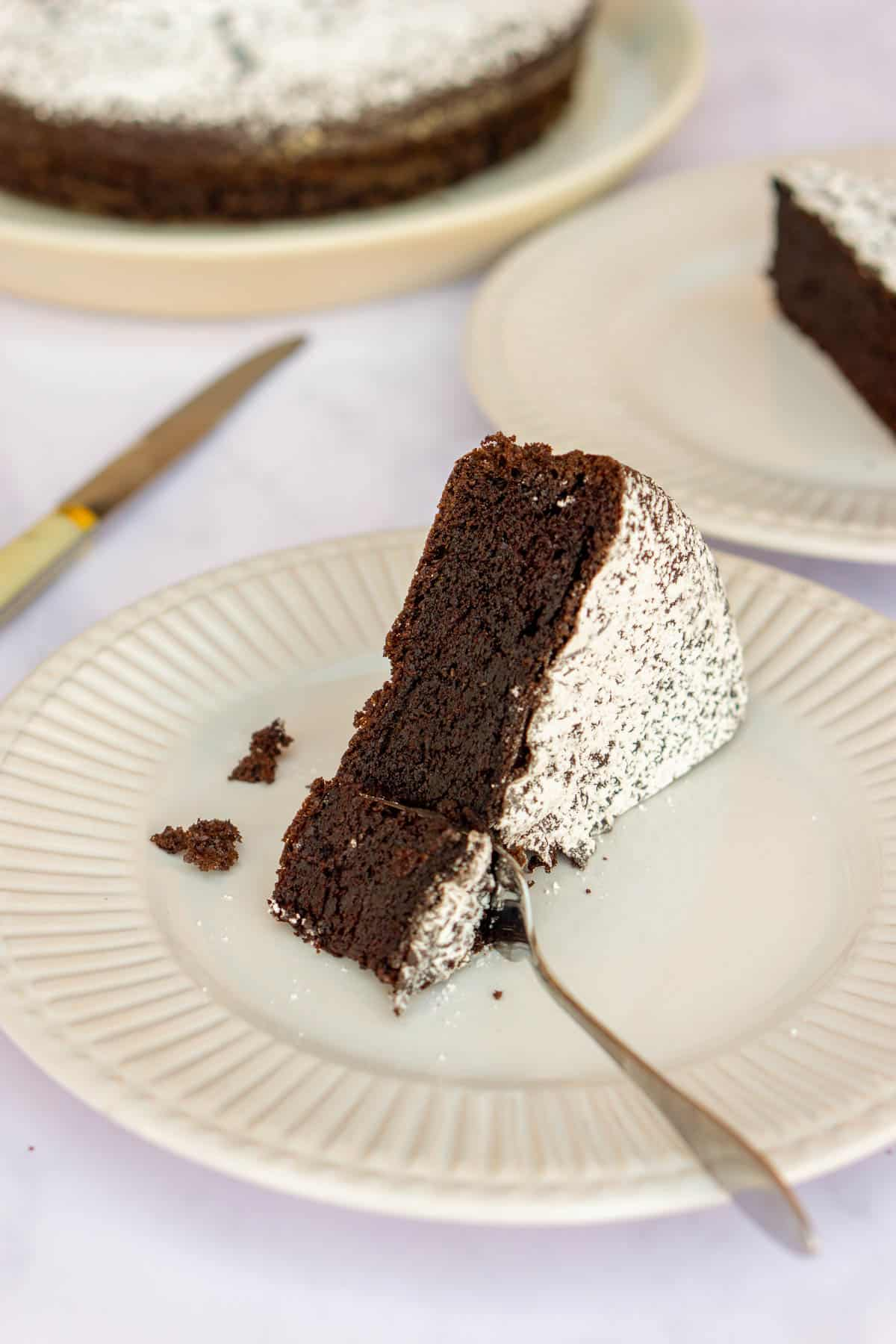 Slice of chocolate olive oil cake on a white plate with more cake in the background