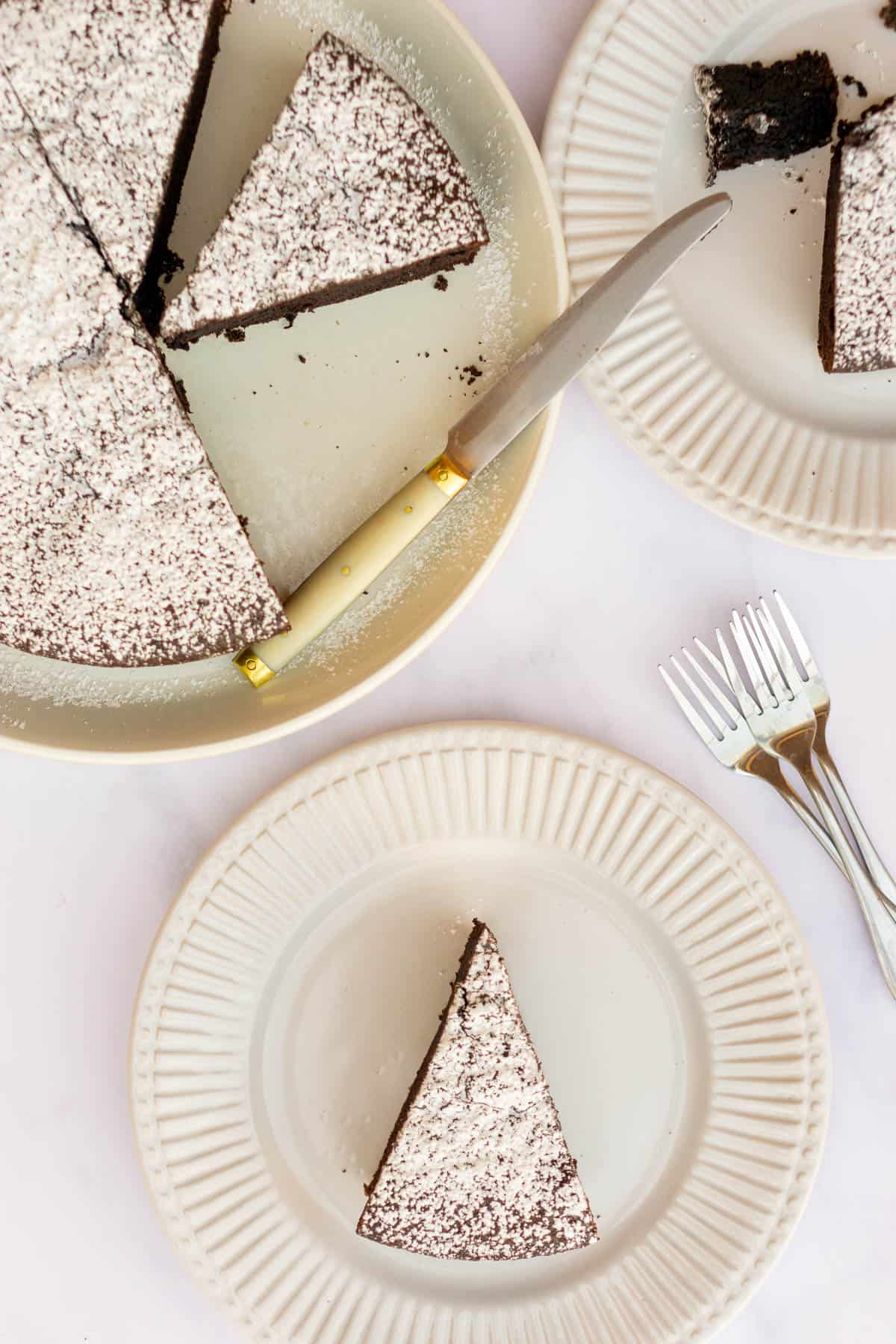 Overhead shot of chocolate olive oil cake cut into slices on a large plate and two smaller slices on small plates.
