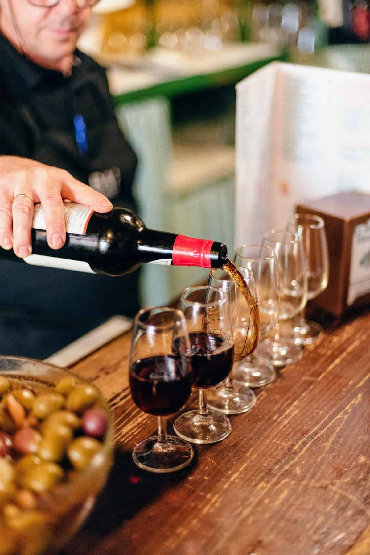 Bartender pouring several glasses of dark brown sherry wine on a wooden bar top