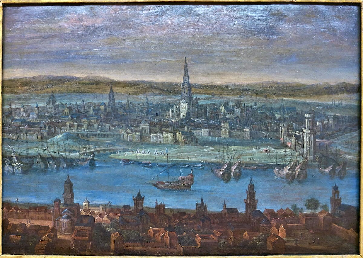 Oil painting of 16th century Seville with large exploration ships in the river in the foreground.