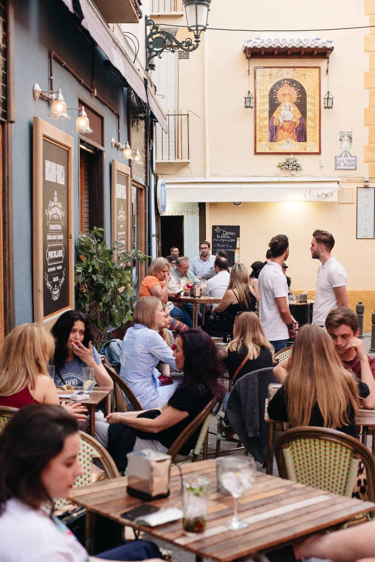 People eating and drinking on a crowded outdoor terrace outside a bar.
