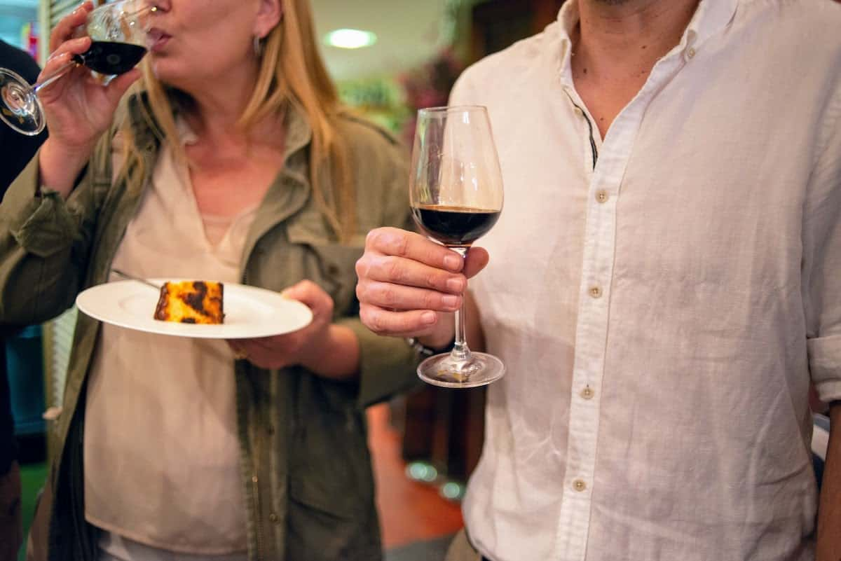 Close up of a man holding a glass of sweet dark wine next to a woman holding a plate of cheesecake.