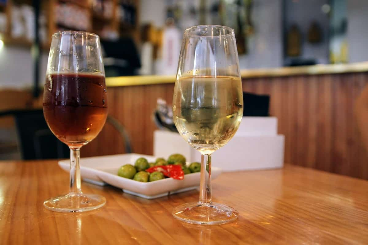 Two glasses of sherry wine, one brown and one pale yellow, on a wooden tabletop in front of a dish of olives.