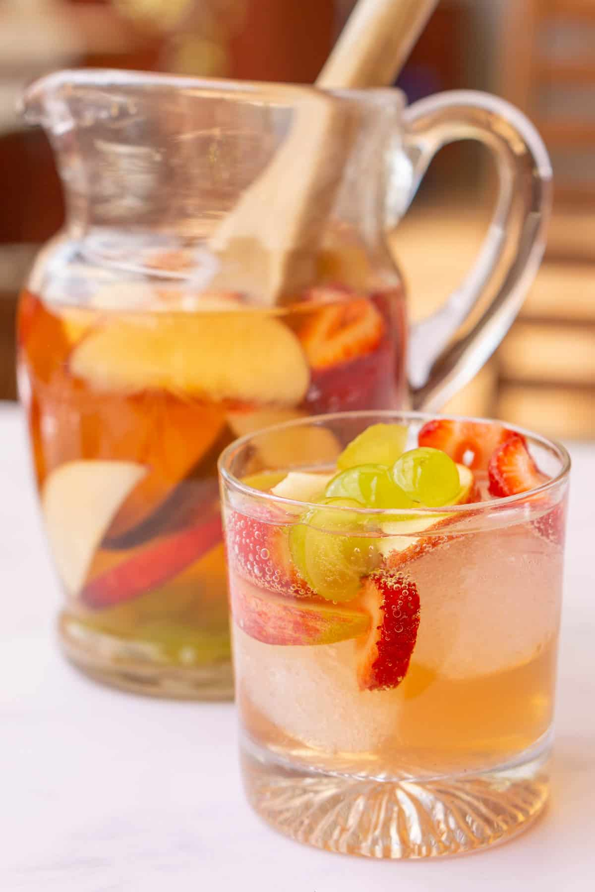 White Wine sangria in a glass pitcher with a wooden spoon. A glass of white sangria with ice in front.