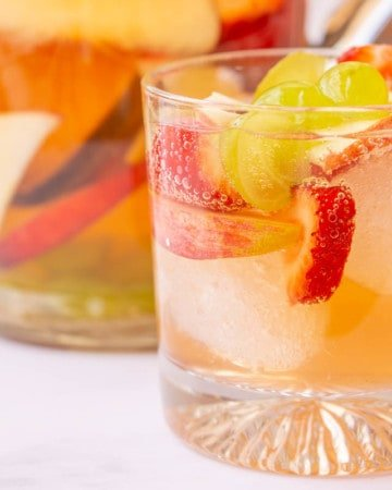 Delicious white wine sangria in a glass with ice cubes and the pitcher behind it.