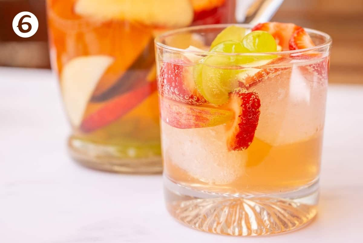 Finished white wine sangria in a glass with ice cubes.