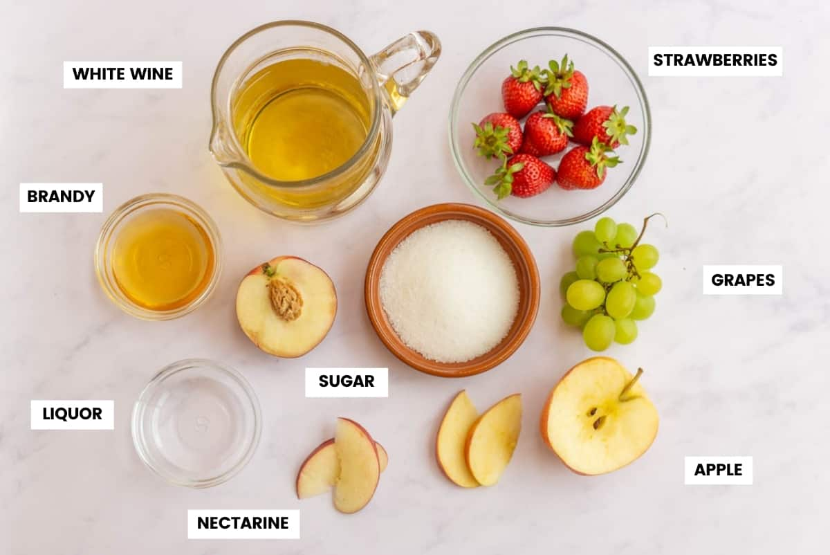 Key ingredients to make white sangria on a white marble countertop. Wine, brandy, liquor, sugar, strawberries, grapes, peach, and apple.