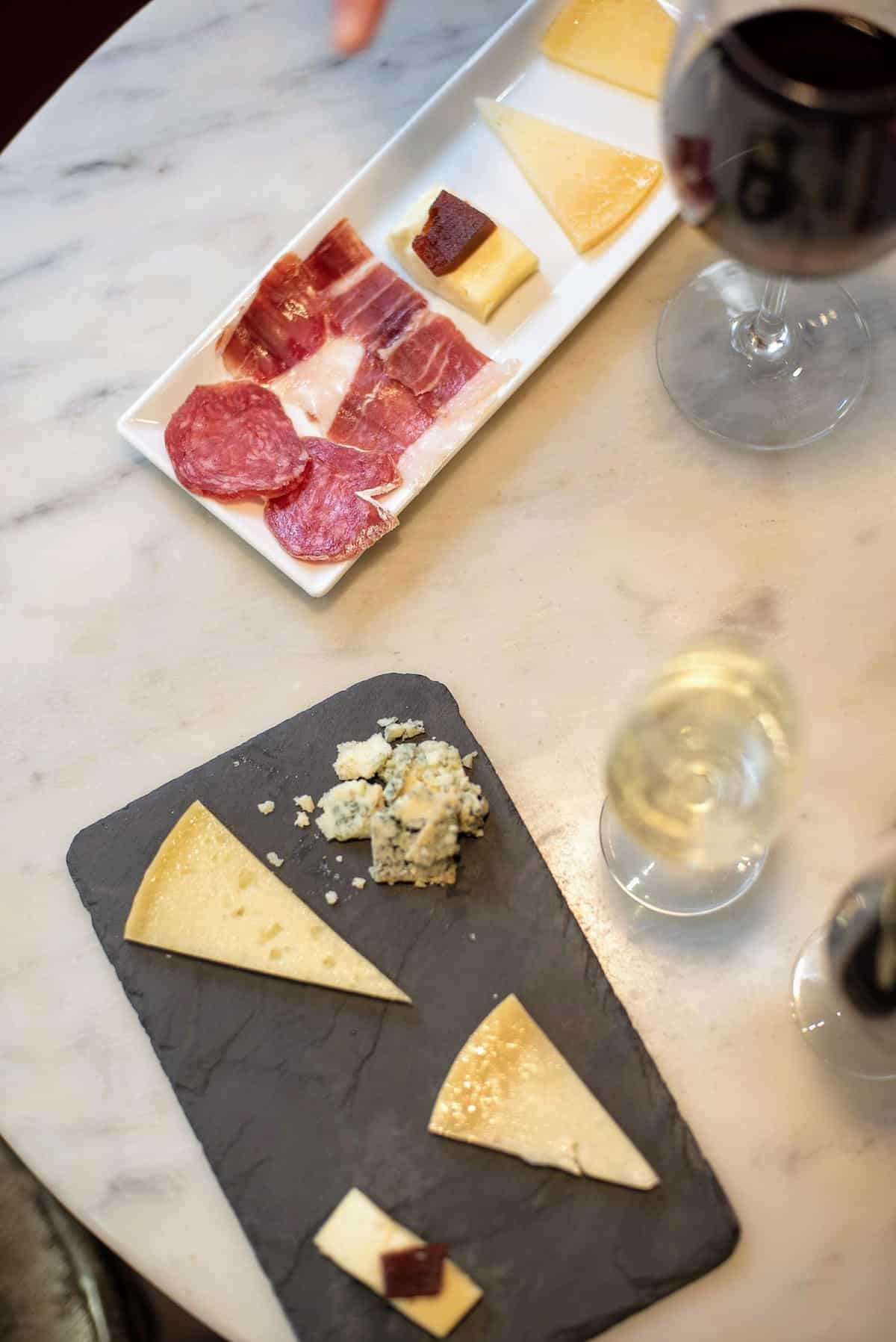 Overhead shot of small cheese and charcuterie trays beside two glasses of wine on a marble tabletop