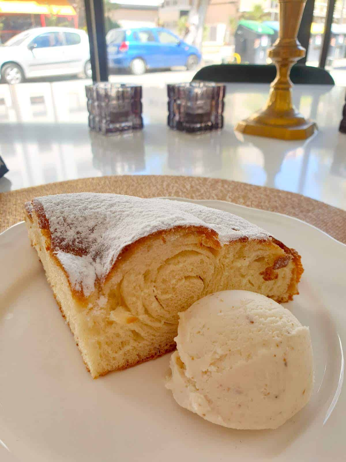 Pastry covered in powdered sugar on a white plate beside a scoop of vanilla ice cream.