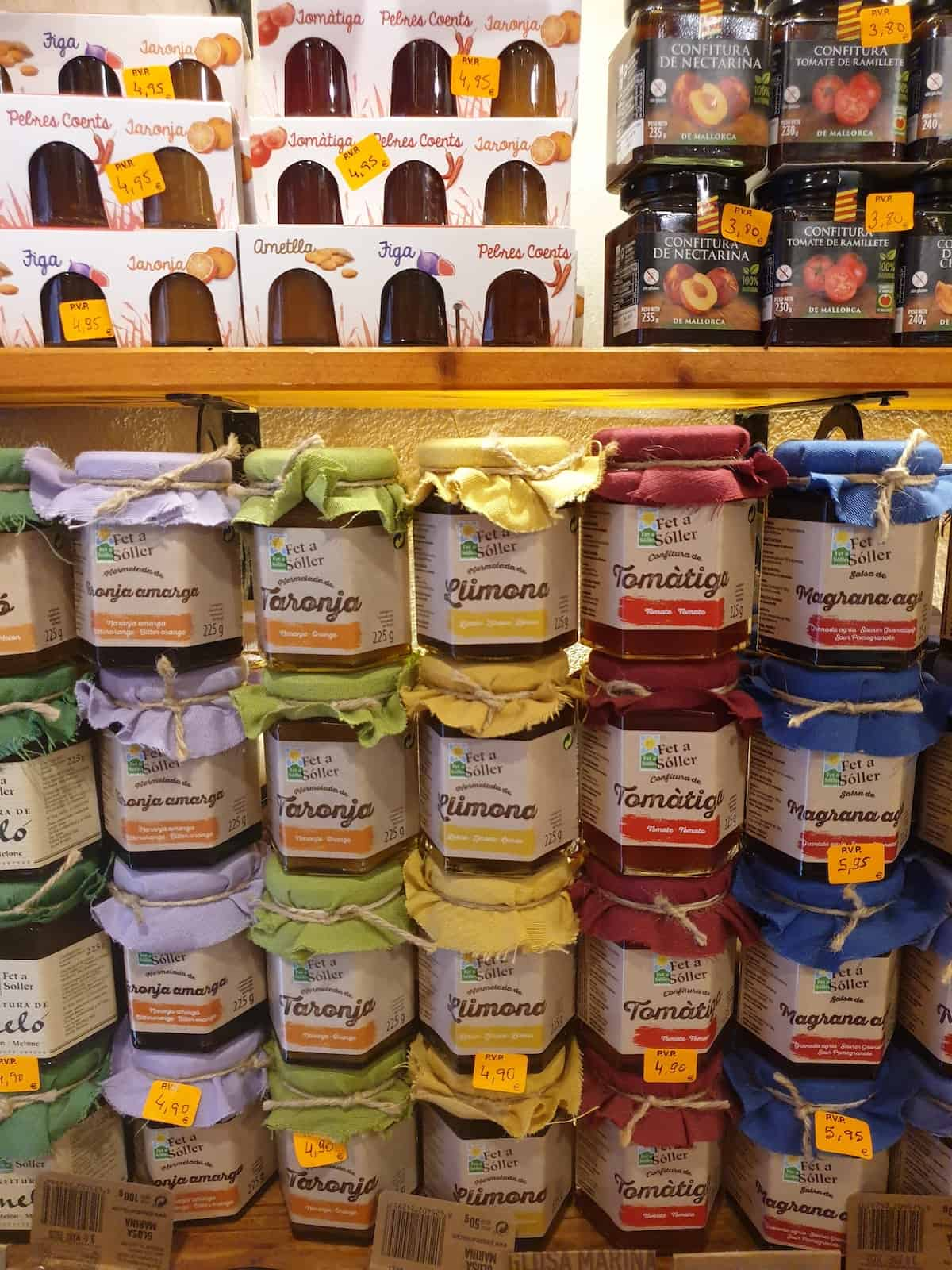 A selection of fruit marmalades and confits with labels in the Mallorcan language on display at a store.