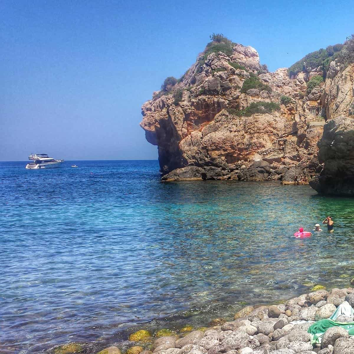 Beach in Mallorca with stones leading into the water and a small rock formation