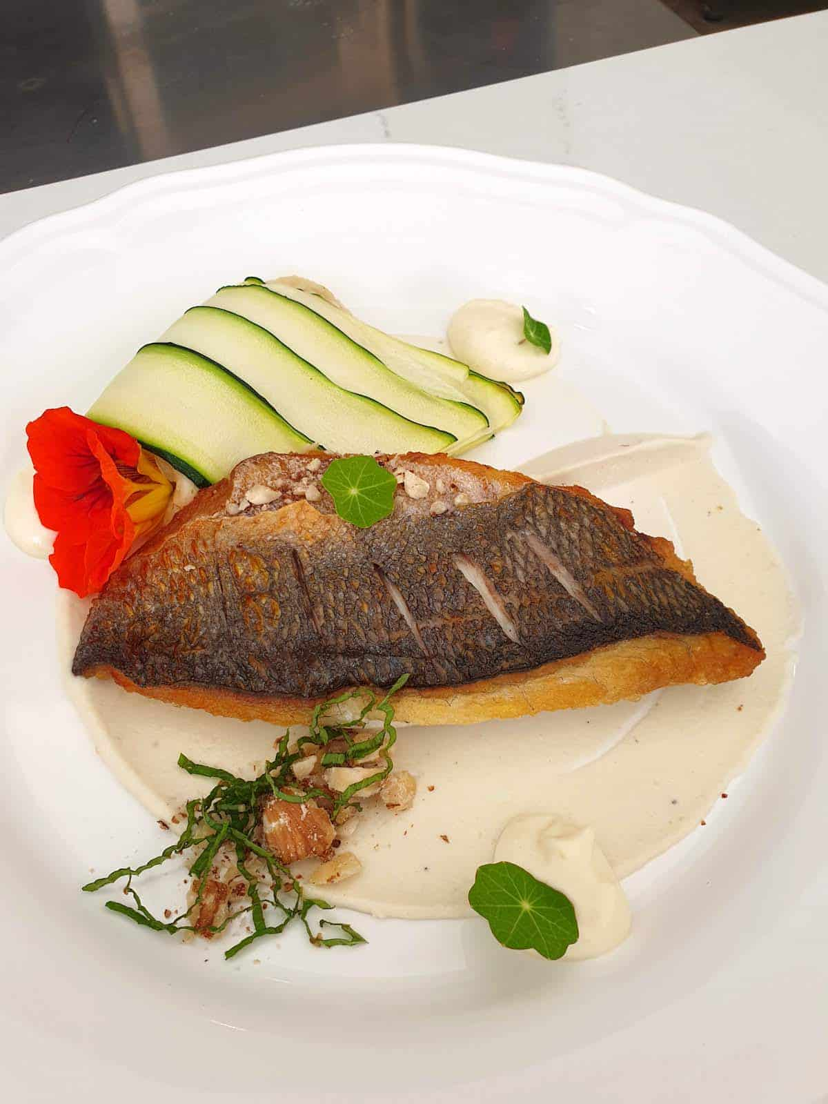 Piece of fish on a white plate garnished with green vegetables, white sauce, and a red flower