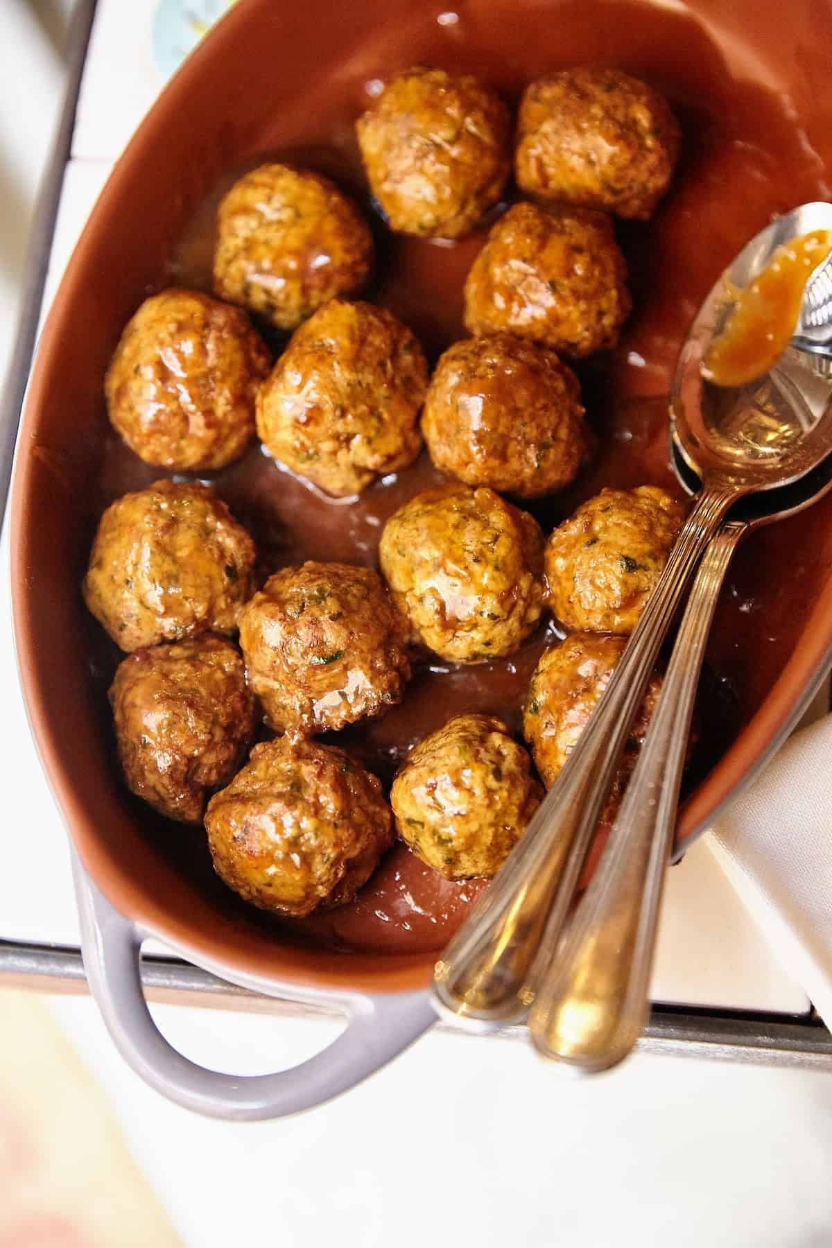 Overhead shot of meatballs in a large brown serving dish