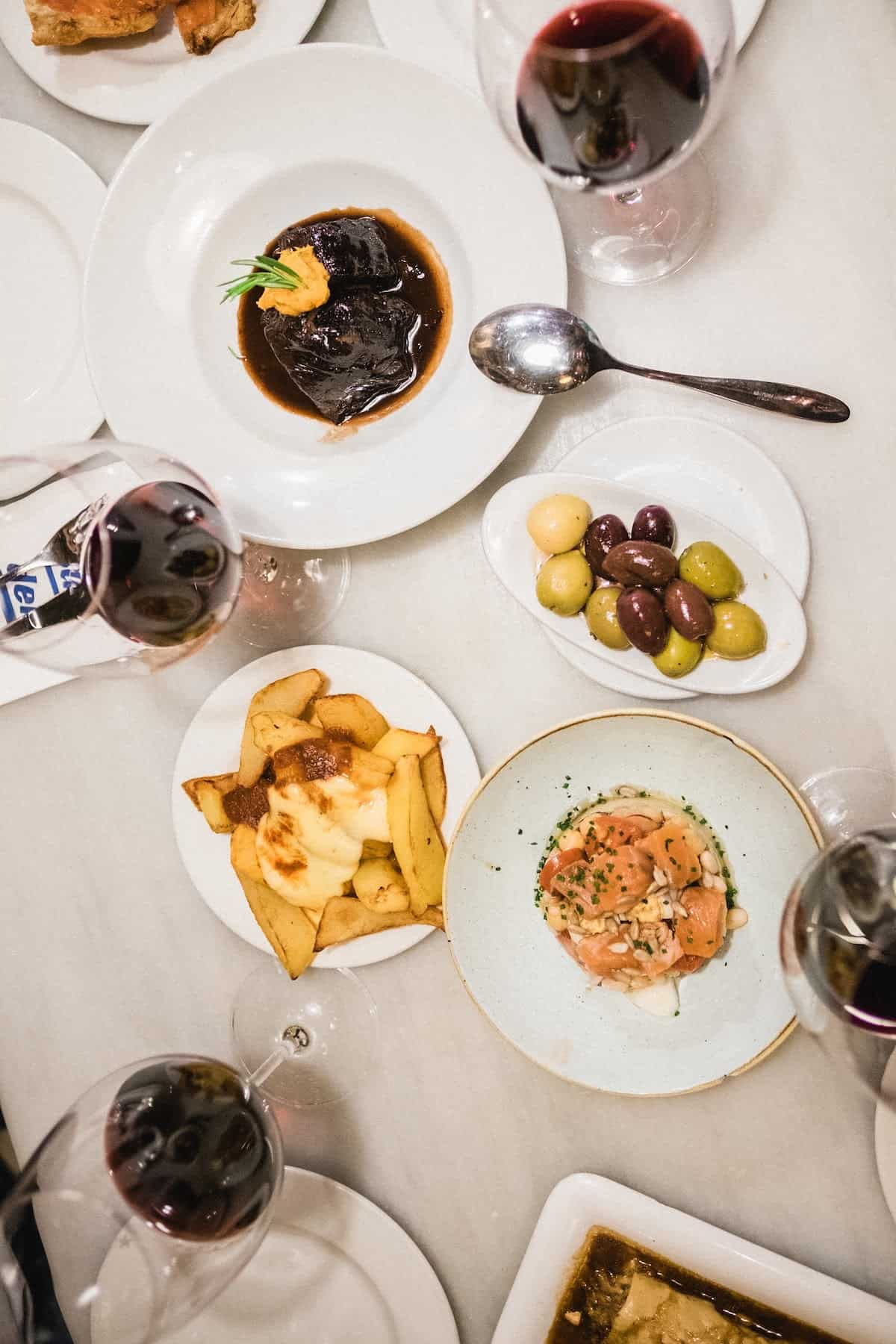 Overhead shot of Spanish tapas and glasses of red wine on a white table
