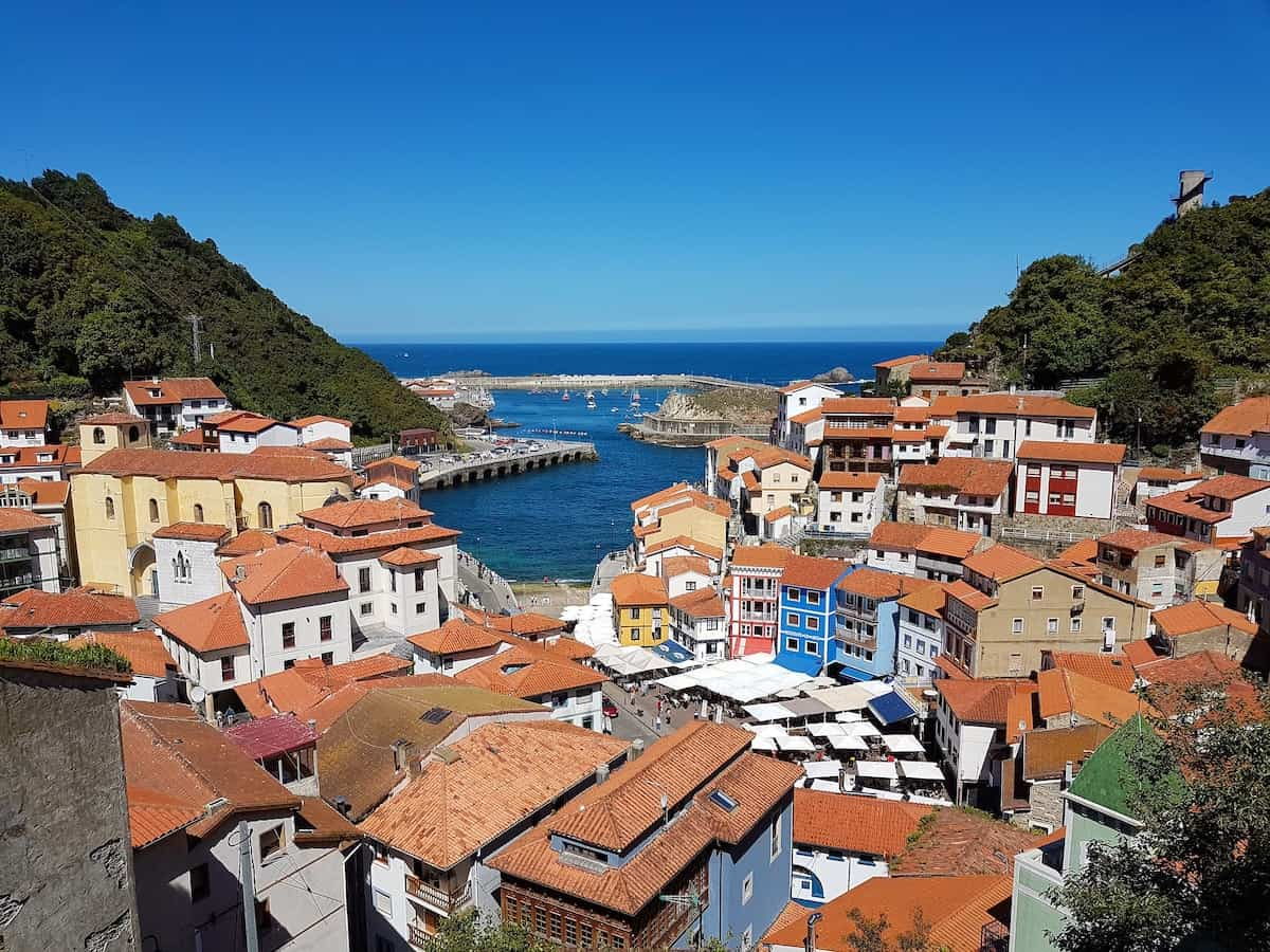 White and blue houses with red tiled roofs overlooking the sea in northern Spain