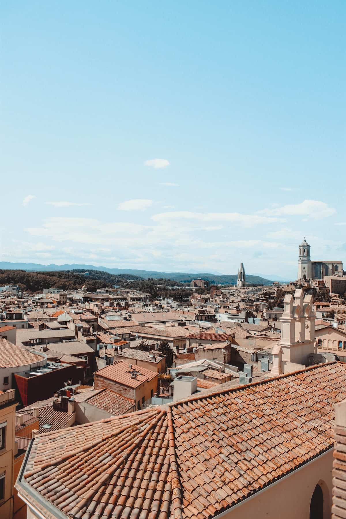 Overhead view of medieval buildings with red tiled roofs in Girona, Spain on a clear day