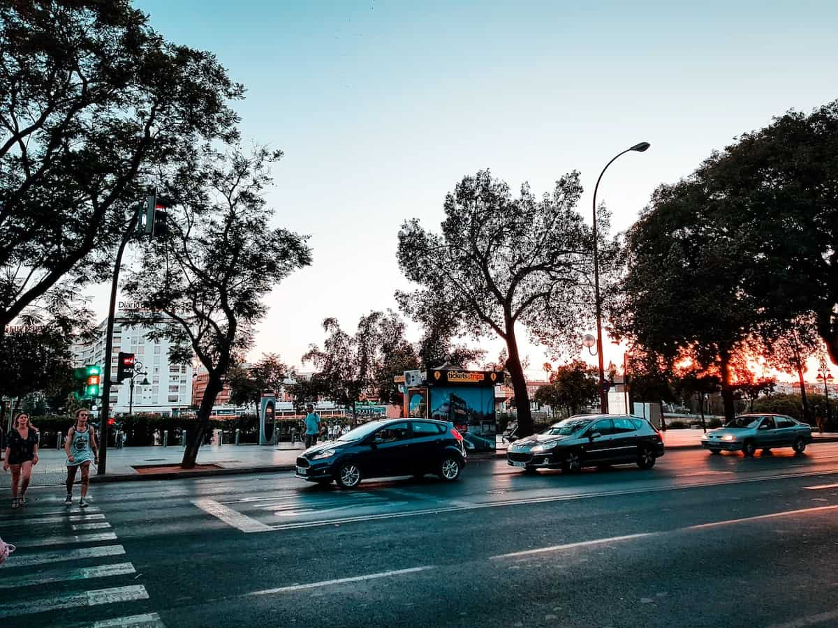 Cars stopped at an intersection on an evening in Seville, Spain